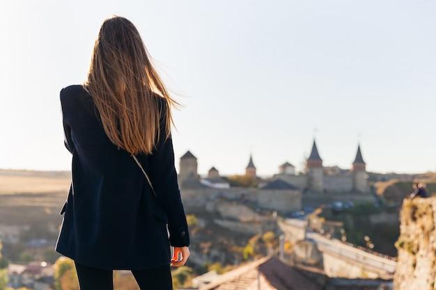 Mädchen zurück, das eine mittelalterliche festung betrachtet