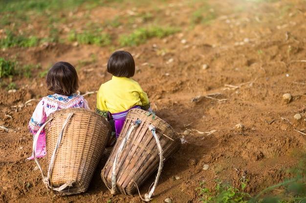 Mädchen zwei, das ein hmong kleid trägt, tragen bambuskorb auf ihr zurück, das auf dem weg zu thei sitzt