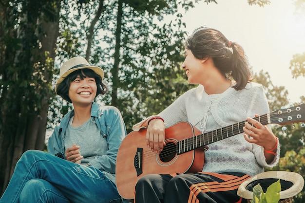 Mädchen zwei, das gitarre und lächeln mit glücklichem in der natur spielt
