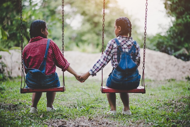 Mädchen zwei, das zusammen auf einem schwingen sitzt