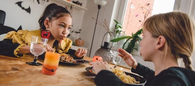 Mädchen zwei im kostüm, das zu mittag isst