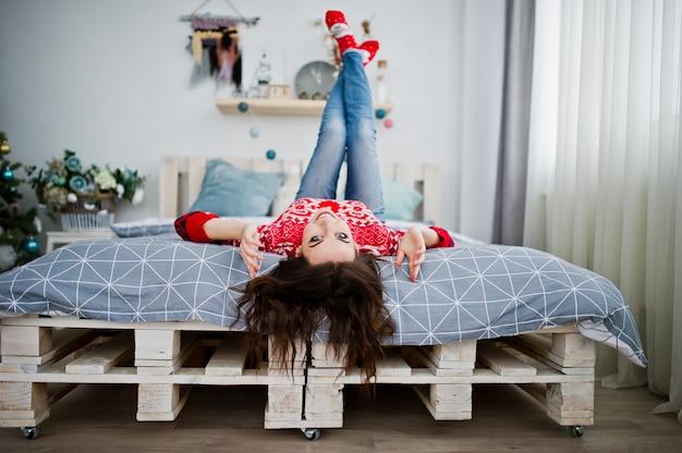 Mädchenabnutzung auf winterstrickjackebett auf raum mit weihnachtsbaum.