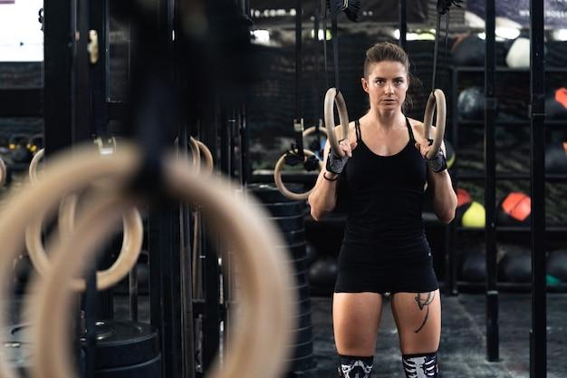 Mädchenathlet, der übung auf den ringen im fitnessstudio vorbereitet. crossfit-training