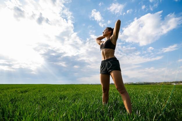 Mädchenathlet macht aufwärmen im freien, übungen für die muskeln. junge frau macht sport, gesunden lebensstil, athletischen körper. sie ist in sportkleidung, schwarzem top und shorts. sportkonzept.