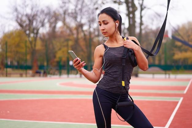 Mädchenathletentraining mit trx auf sportplatz