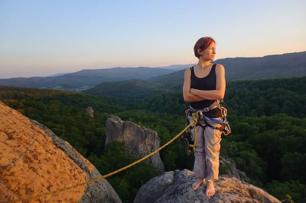 Mädchenbergsteiger auf bergspitze auf großer höhe am abend