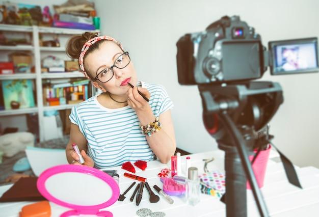 Mädchenblogger zeichnet auf einer digitalkamera auf, die über kosmetik, lippenstift spricht.