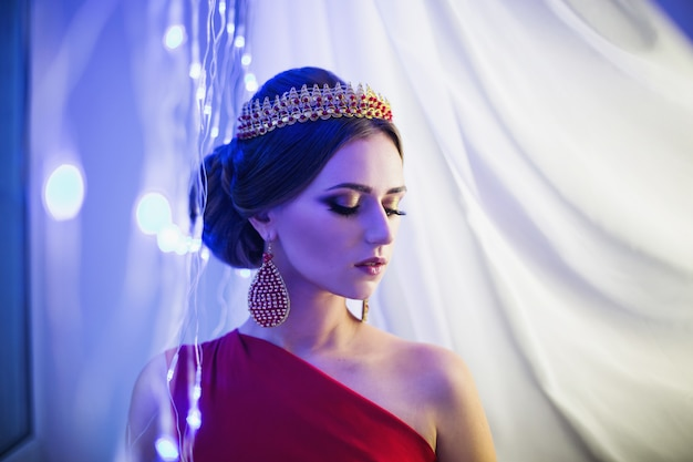 Mädchenbrünette in einem roten kleid mit schöner frisur, perlenohrringen und einer krone auf ihrem kopf und hellem make-up. weiblicher stil. mysteriöse frau. blaues licht