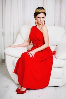 Mädchenbrünette in einem roten kleid mit schöner frisur, perlenohrringen und einer krone auf ihrem kopf und hellem make-up. weiblicher stil. mysteriöse frau.
