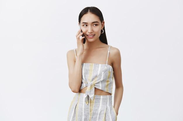 Mädchenbuchungstisch per telefonanruf, blick nach rechts beim sprechen auf dem smartphone stehend in trendigen passenden kleidern über graue wand