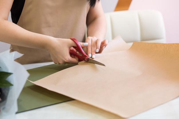 Mädchenfloristin, die schere benutzt, verziert einen blumenstrauß in einem blumenladen