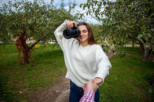 Mädchenfotograf in einem weißen pullover und jeans macht ein foto mit einer professionellen kamera im park