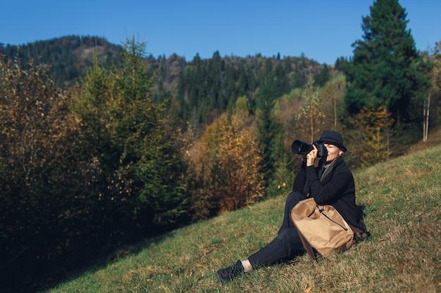 Mädchenfotografin mit rucksack sitzt am hang und schießt im herbst in die berge.