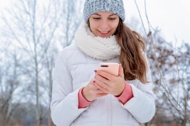 Mädchenfrau im freien, die online-blogger des weißen hutrosas des telefonwinterschnees kalten weißen verwendet