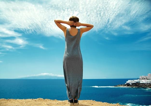 Mädchenfrau in lässiger hipster-kleidung, die auf der klippe des berges steht