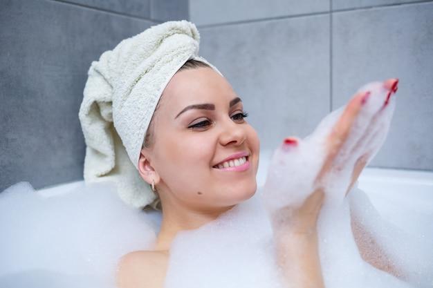 Mädchenfrau mit einem weißen handtuch auf dem kopf liegt im badezimmer in einer weißen badewanne. in den händen von viel schlammiger seife. voller whirlpoolschaum. entspannen sie sich nach einem anstrengenden tag. entspannungsbehandlung im spa