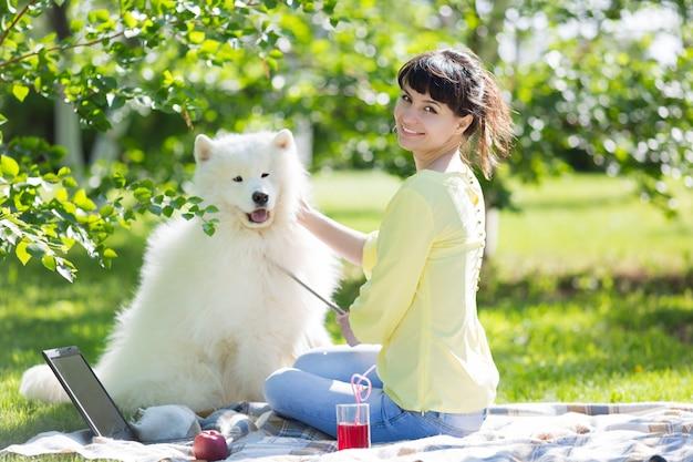 Mädchenfreiberufler mit einem großen weißen hund.