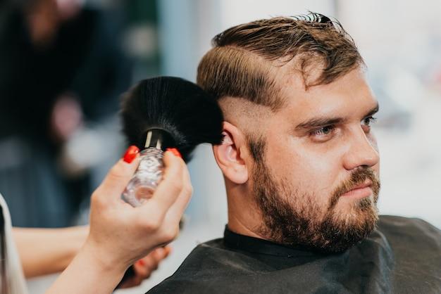 Mädchenfriseur entfernt haarreste mit einer bürste, nachdem er geschnitten hat