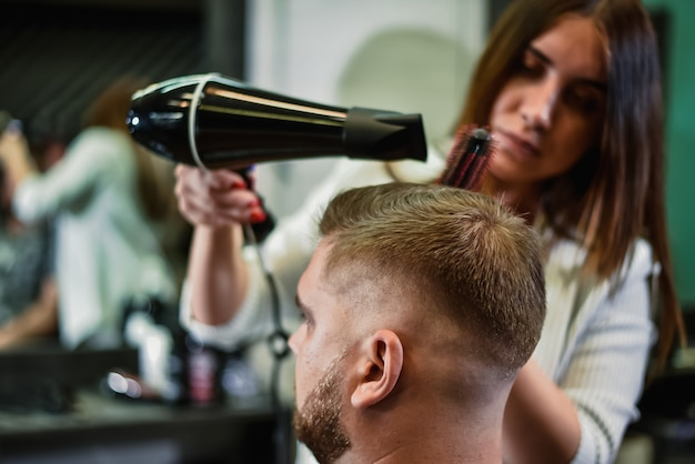 Mädchenfriseur trocknet einem mann in einem salon haar
