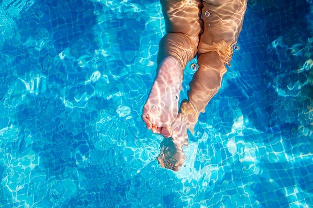 Mädchenfüße in einem blauen schwimmbad im sommer, kopieren raum.
