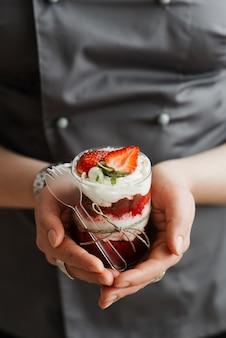 Mädchengebäckkoch, der pudding in einer glasschale nahaufnahme hält