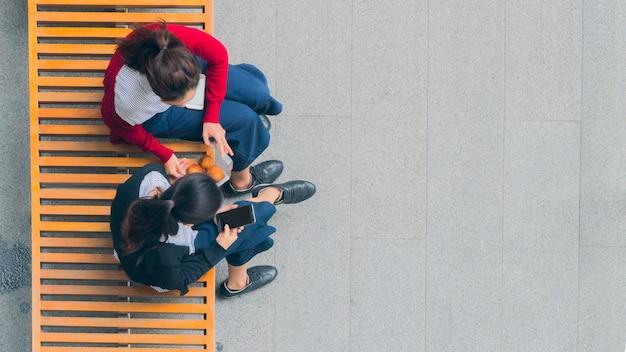 Mädchengruppe benutzen intelligentes telefon und sprechen auf holzbank