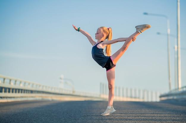 Mädchengymnast beschäftigt im sommer auf der straße, auf einem hintergrund des blauen himmels, schnur, dehnung, arabeske
