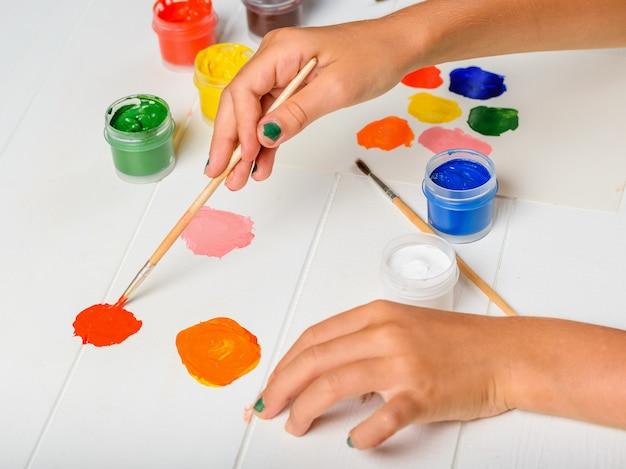 Mädchenhände, die die rote farbe in der palette auf einem weißen tisch aufheben.