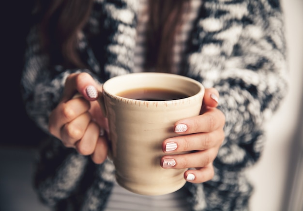 Mädchenhände halten eine tasse kaffee und