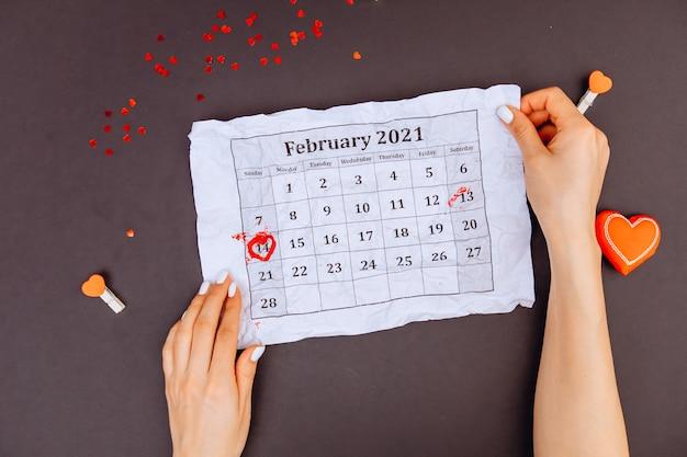 Mädchenhände halten einen kalender mit eingekreistem 14. februar draufsicht. valentinstag. ein kreis von süßigkeiten aus kars herzen.
