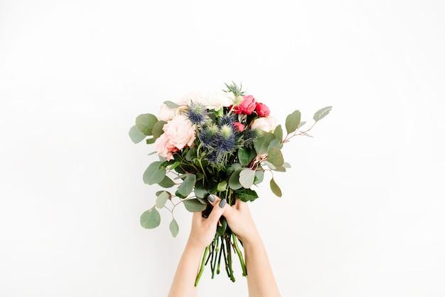 Mädchenhände halten schöne blumenstrauß bombastische rosen, blaues eringium, eukalyptus, isoliert auf weißem hintergrund. flache lage, ansicht von oben