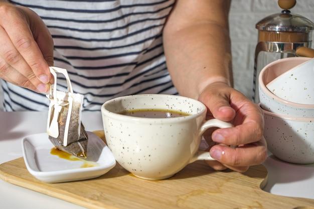 Mädchenhände im rahmen, nahaufnahme, machen sofortige frisch gebrühte tasse kaffee aus der tasche. trendige auswahl an tropfkaffee, in einer hellen küche auf einem tisch mit tassen, morgensonne