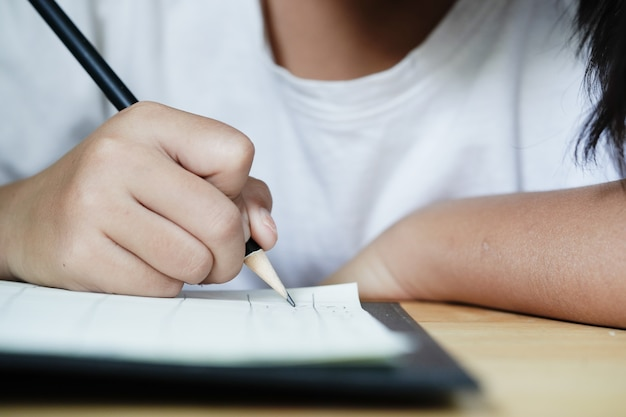 Mädchenhände machen hausaufgaben in der mathematik.