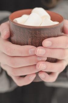 Mädchenhände mit dünnen fingern halten eine braune tasse kaffee mit marshmallows, getönt und verblasst
