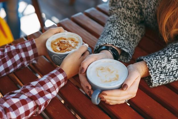 Mädchenhände mit sommersprossen, die tassen kaffee halten