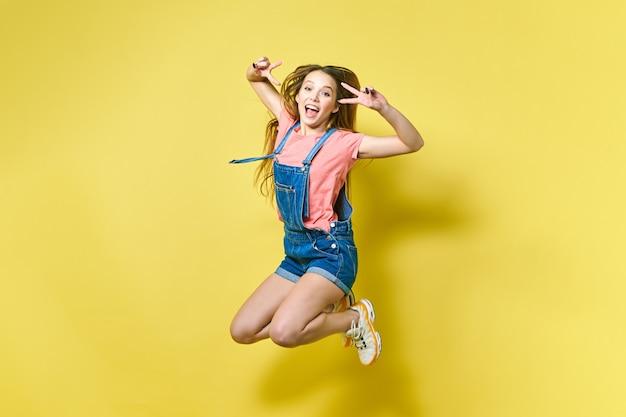 Mädchenhaft, funky, glück, traum, spaß, freude, sommerkonzept. sehr aufgeregtes glückliches süßes mädchen springt im sommeroutfit auf gelbem hintergrund auf