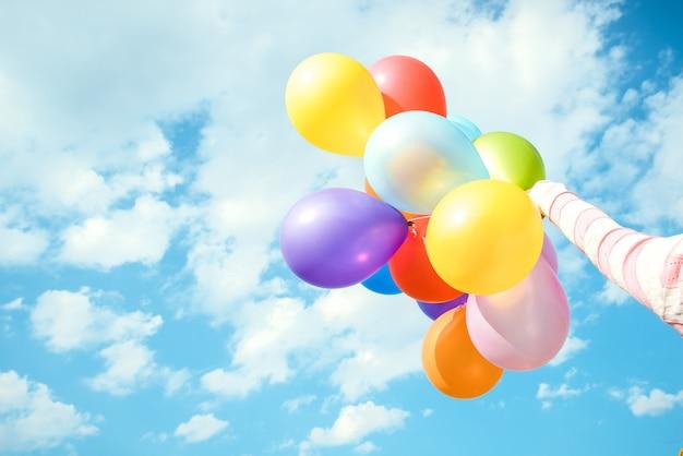 Mädchenhand, die mehrfarbenballone erfolgt mit einem retro- instagram filtereffekt, konzept des glücklichen geburtstags im sommer und hochzeitsflitterwochenparty, weinlesefarbtonart hält