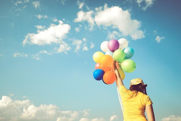 Mädchenhand, die mehrfarbenballone hält
