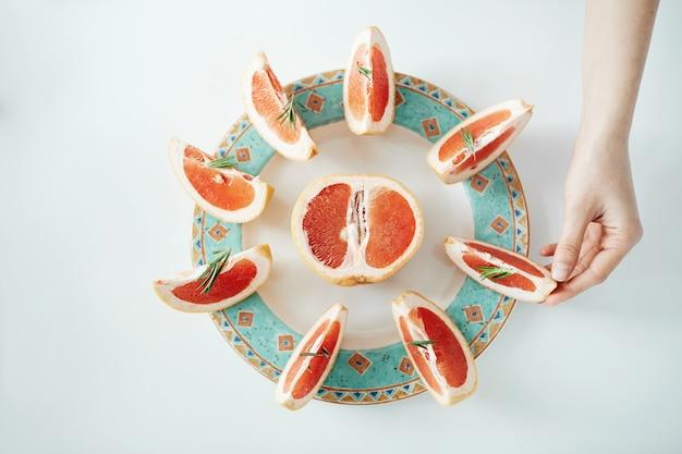 Mädchenhand, die scheibe grapefruit vom weißen teller nimmt. von oben. gesunde ernährung.