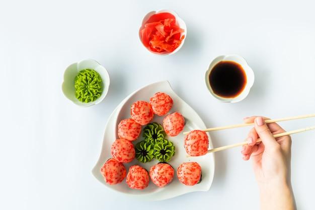 Mädchenhand hält rotes sushi über weißem teller