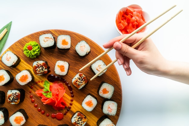 Mädchenhand hält sushi über der holzoberfläche