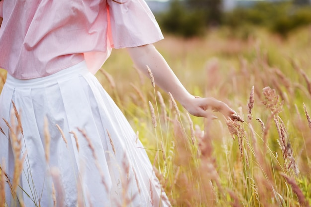 Mädchenhand im sommerfeld. mädchen streichelte weizen