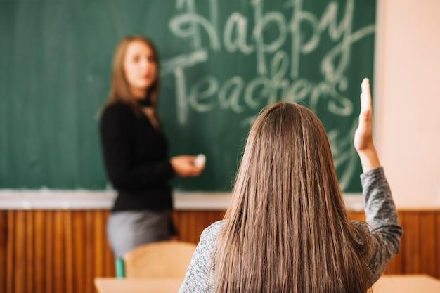 Mädchenhand oben im klassenzimmer