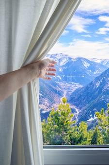 Mädchenhand zieht den vorhang zurück, um die berge im fenster zu sehen.