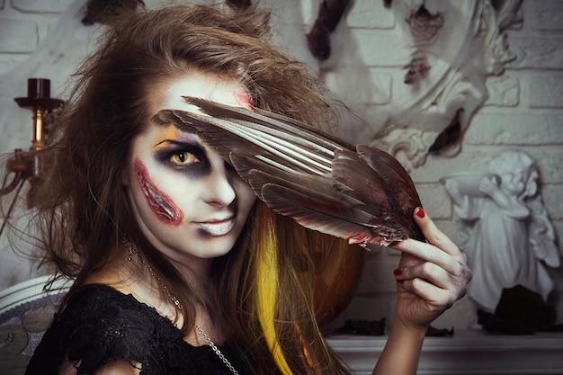 Mädchenhexenzombie isst den vogel vor halloween. hexe bereitet sich auf die feiertagsnächte der toten vor