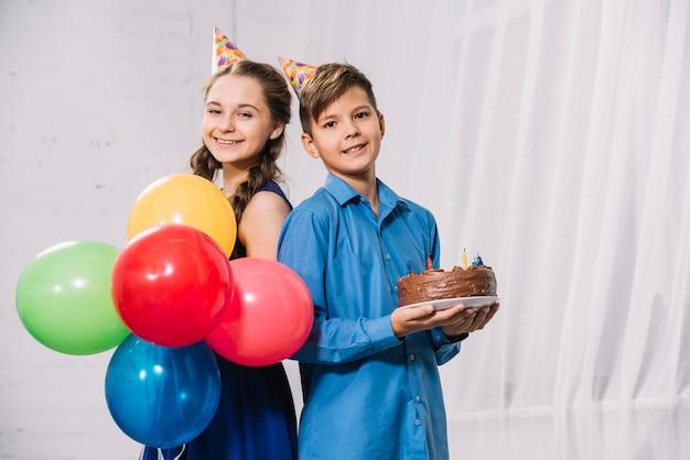 Mädchenholdingballone und junge, die den geburtstagskuchen stehen zurück zu der rückseite hält, die kamera betrachtet