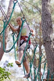 Mädchenjugendlicher mit kletternder ausrüstung in einem seilunterhaltungspark