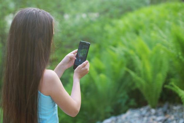 Mädchenjugendlicher mit langen haaren schaut auf dem hintergrund von farndickichten in das smartphone.