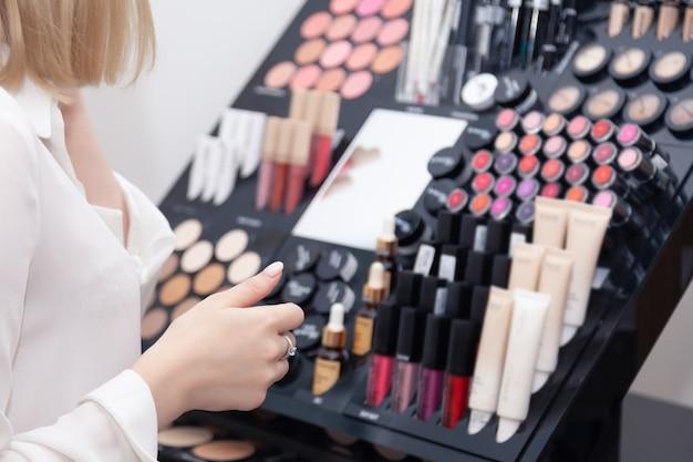 Mädchenkäufer, verkäufer, maskenbildner, visagiste an des gestells mit verschiedener dekorativer kosmetik. anzeige professioneller kosmetikladen, make-up-studio