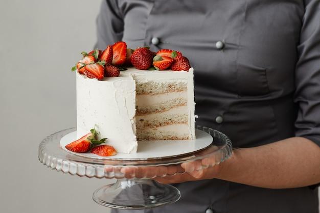 Mädchenkellner, der ein tablett mit einem weißen kuchen hält, der mit erdbeeren ohne ein stück verziert ist
